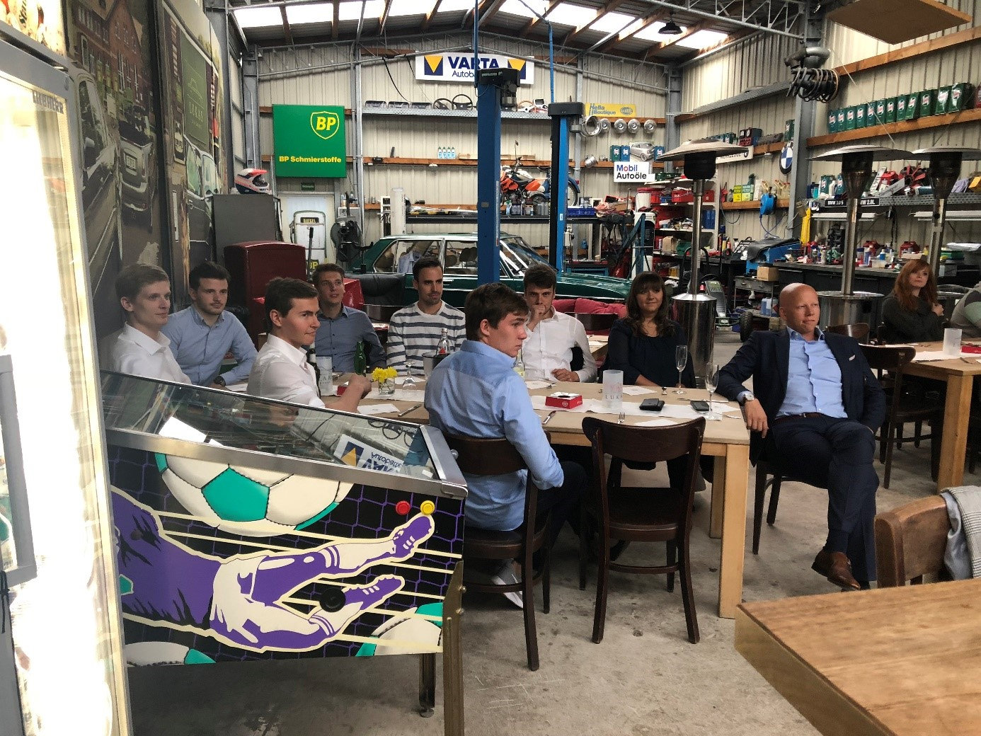 group of a diverse group of people listening to a talk, flipper machine can be seen in the front of the picture